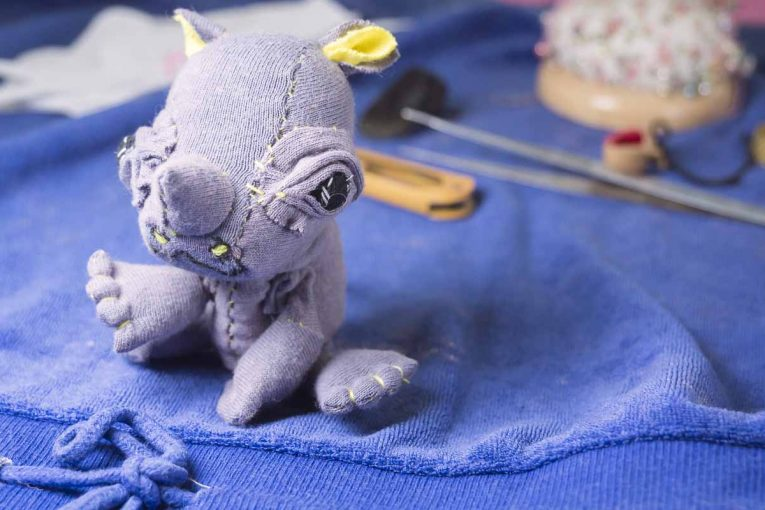 baby rhino upcycled textile doll sitting on the desk playing