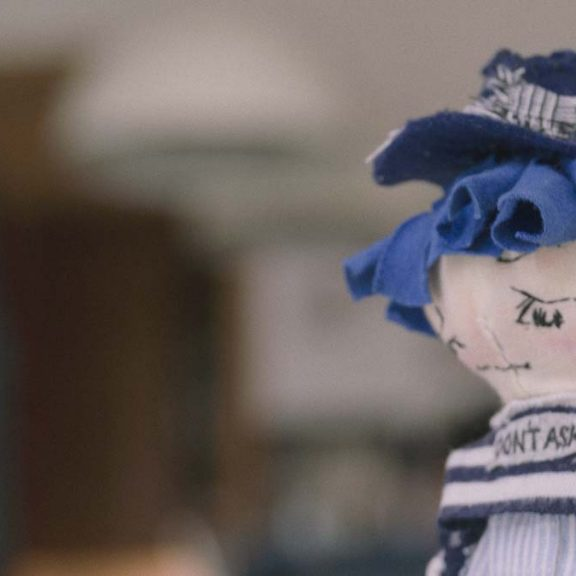 mini pocket girl doll with blue hair, looking down, contemplating