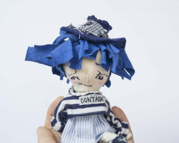 grumpy girl doll with blue hair and fedora hat