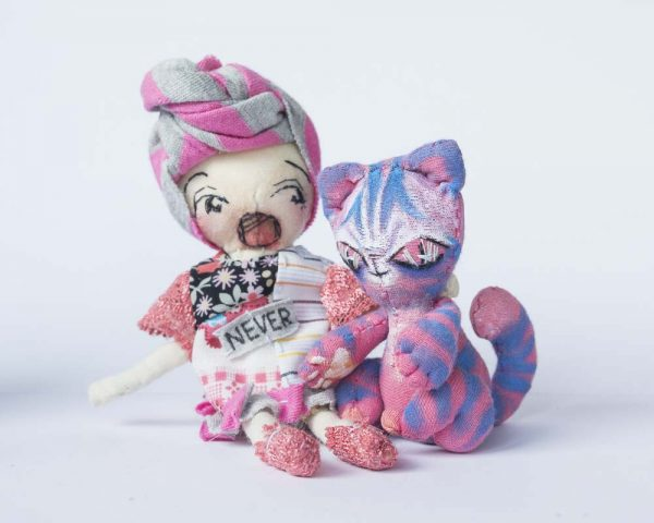 pink girl doll with ruban sitting with her alien cheshire cat