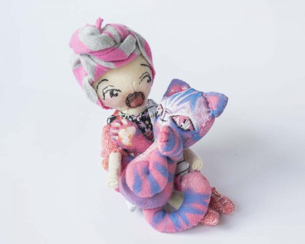 girl doll mini handmade by doll artist, cuddling her alien cehshire cat in pink and purple