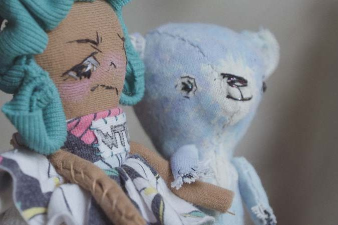 a small girl doll holds the hand of an artist's bear