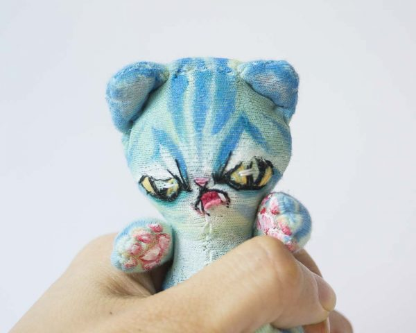 turquoise alien cat hand made doll held in one hand