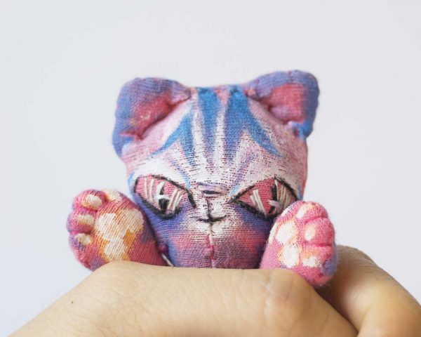 pink alien cat held in one hand showing its small size
