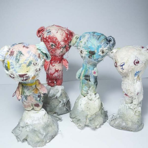 group of four artist teddy bears each reaching the heights