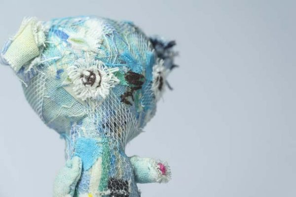 side view of a turquoise little teddy bear, hand stitched and collaged by doll artist Marn Wong