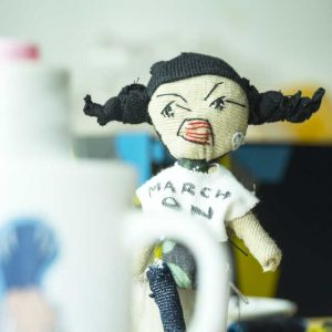 A black haired feminist textile art doll girl marching forward, wearing a protest slogan t-shirt
