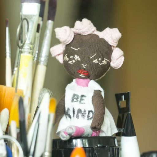 a textile art doll girl with multi mini bun wearing a slogan t-shirt Be Kind.