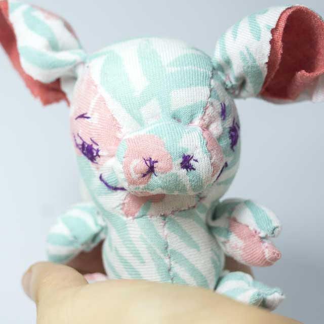 front view of a happy piglet plushie with wings from tropical print reclaimed fabric