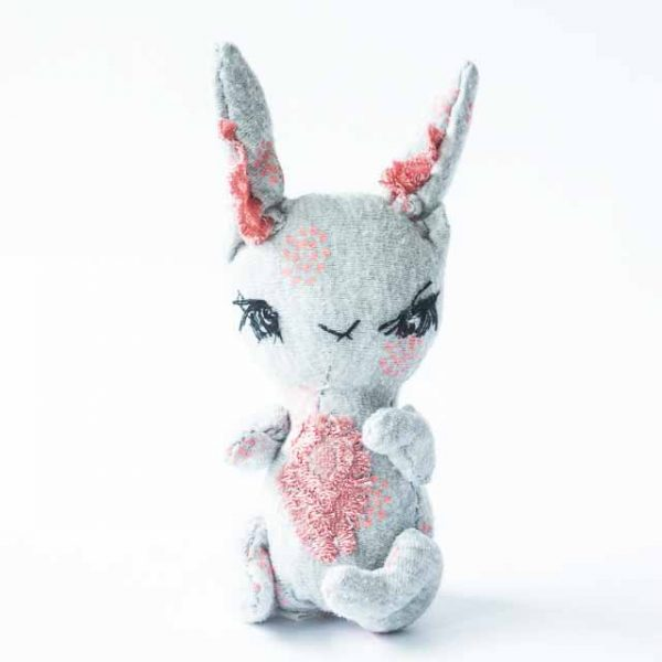 a tiny grey rabbit pocket art doll looking determined