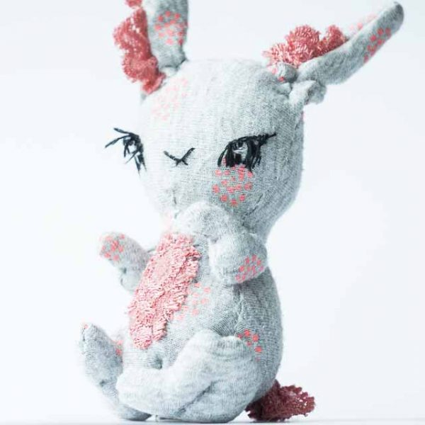 a grey and pink rabbit art doll with long eye lashes