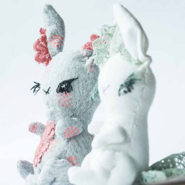 2 handmade artist bunny pocket dolls sitting side by side looking at the horizon