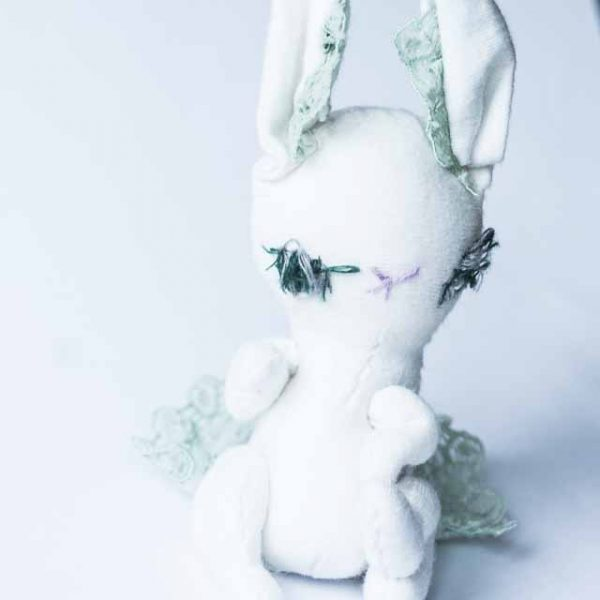 this white bunny doll looks rather moody, looking away from the camera