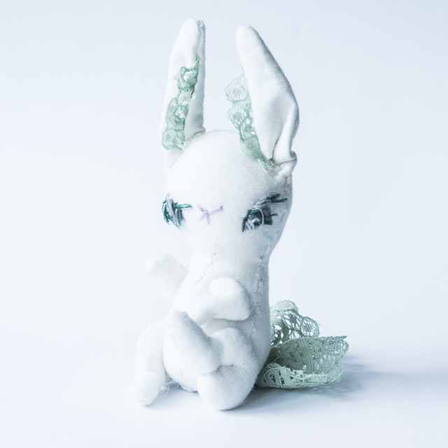 a white bunny doll with long eye lashes slouching on the ground