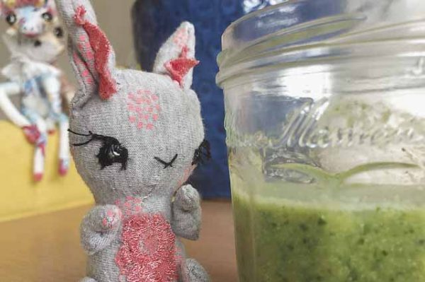 handmade bunny art doll looking at a green smoothie