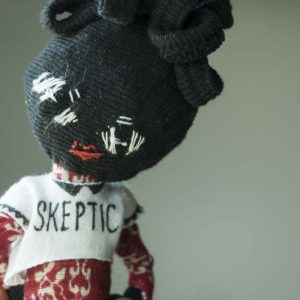 A deep skintone doll wearing a skeptic slogan t shirt looks at the camera with a head tilt.
