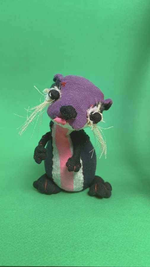 textile artist doll of Gladys the otter with tilted head and cute chubby fingers