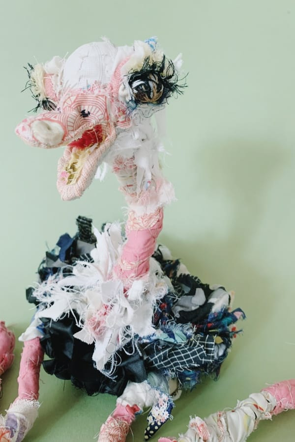 slow stitched and visibly mended ostrich textile doll, sit down with legs bent backwards. made of recycled old clothes.