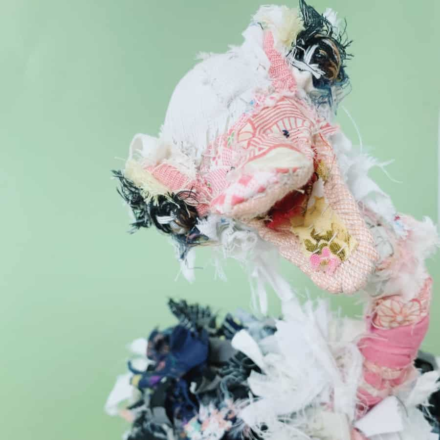 ostrich textile artist doll with big eyes and feathers looking straight at the camera