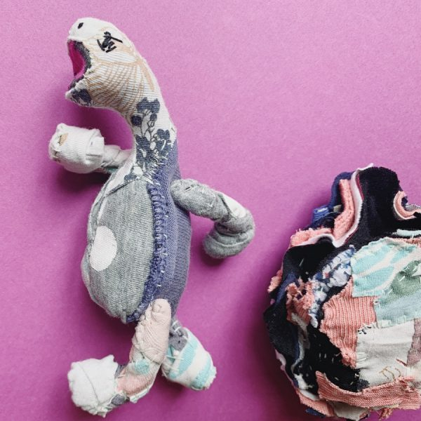 a textile art doll tortoise walks away from his patchwork style shell