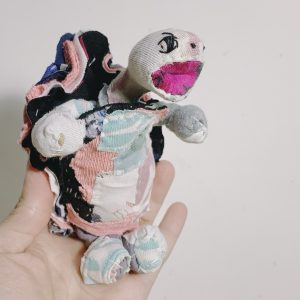 textile art doll tortoise strains his neck and opens his mouth appears to be shouting at the top of his lungs