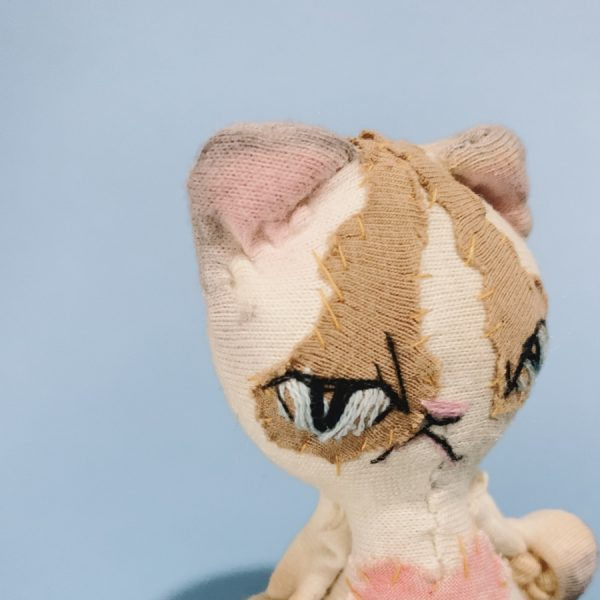 a headshot of a grumpy ragdoll cat textile art doll