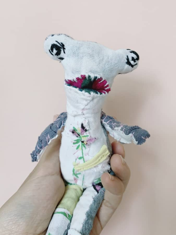 hammerhead artist textile doll held in a hand, shows visible mending, slow stitching and hand quilted elements, made entirely of old clothes