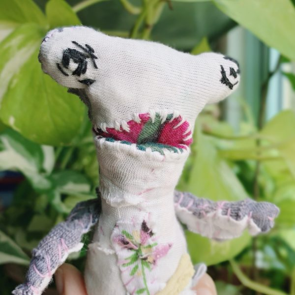 hammerhead with teeth, an artist textile doll with embroidery eyes, looks far ahead. completely hand stitched using recycled materials