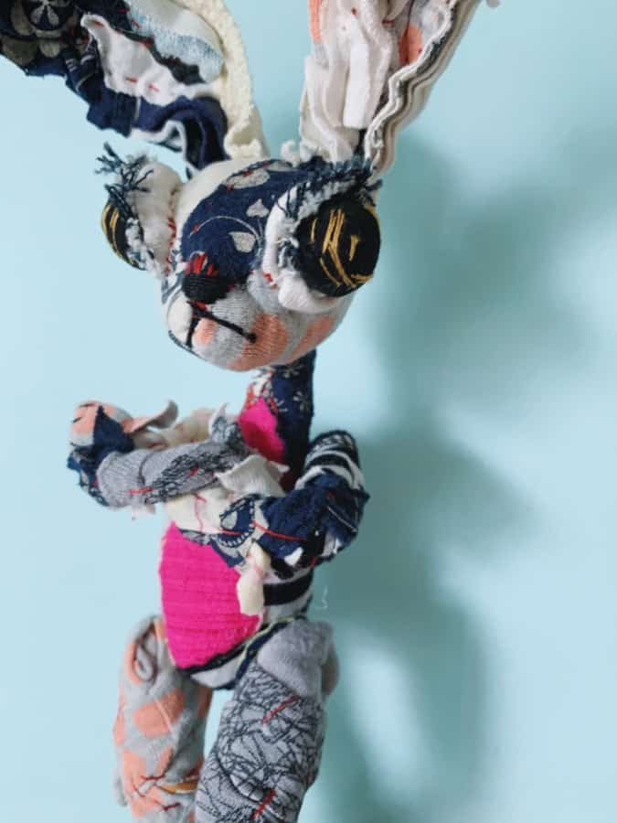 jackrabbit textile art fabric doll leans against the wall with her arms crossed