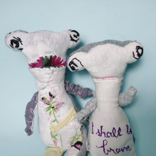 2 hammerhead art dolls, one meek and another vocal, handmade of upcycled old clothings