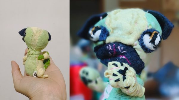 a picture showing curly tail on the back; face and paw of a pug textile art doll with protruding eyes, made of recycled materials