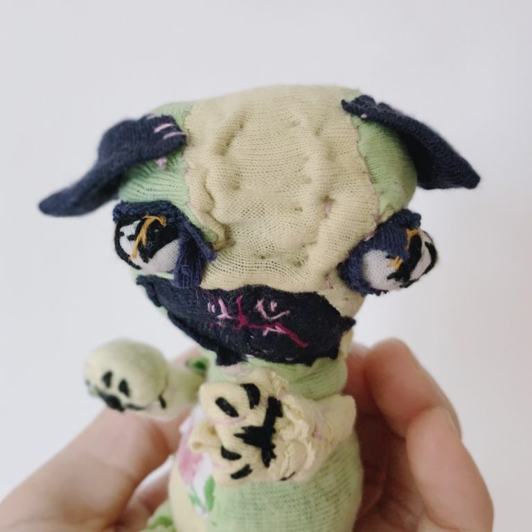 stoic and silly pug textile art doll showing two front paws, protruding eyes. hand stitched from upcycled clothes.