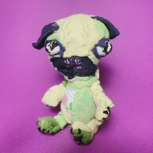 stoic and silly pug art textile doll slow stitched using recycled clothes, in lemon, lime, and floral
