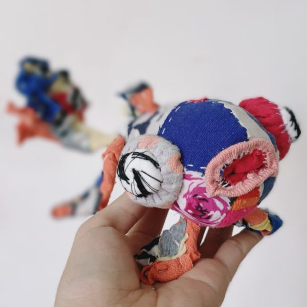 hand holding bright goldfish textile art doll made with recycled fabric and slow stitched