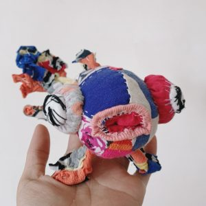 goldfish textile artist doll held in a hand, handstitched in bright colorful upcycled fabric