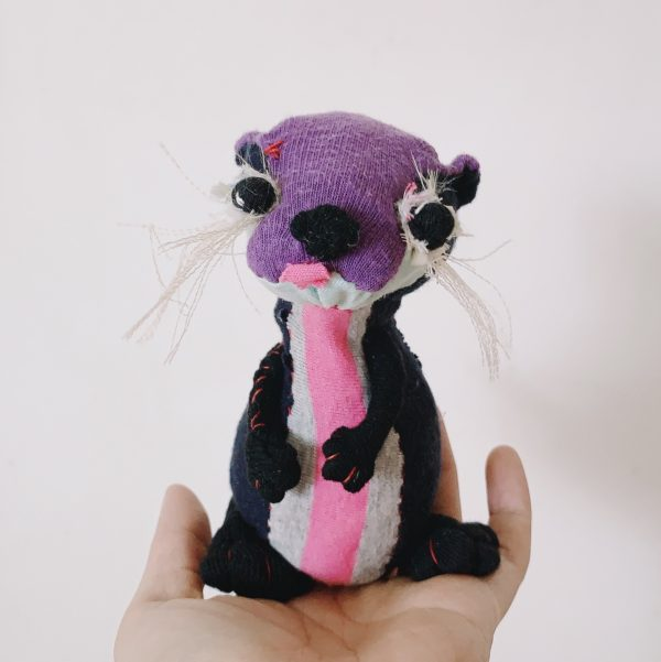 textile art doll of an otter slow stitched from upcycled fabric, tongue out with hands in front of the belly
