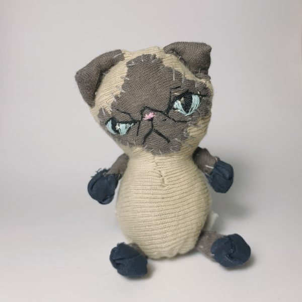 Fat exotic short hair cat doll with seal point colours looking very grumpy