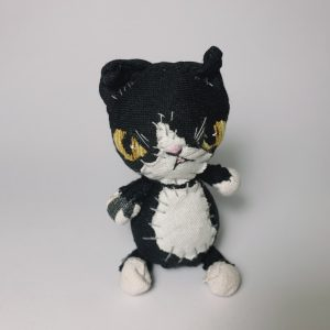 Tuxie cat handmade textile soft sculpture looking grumpy at the camera