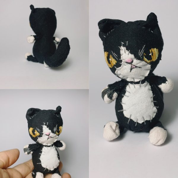 soft sculpture of a tuxedo cat, made of recycled old clothes
