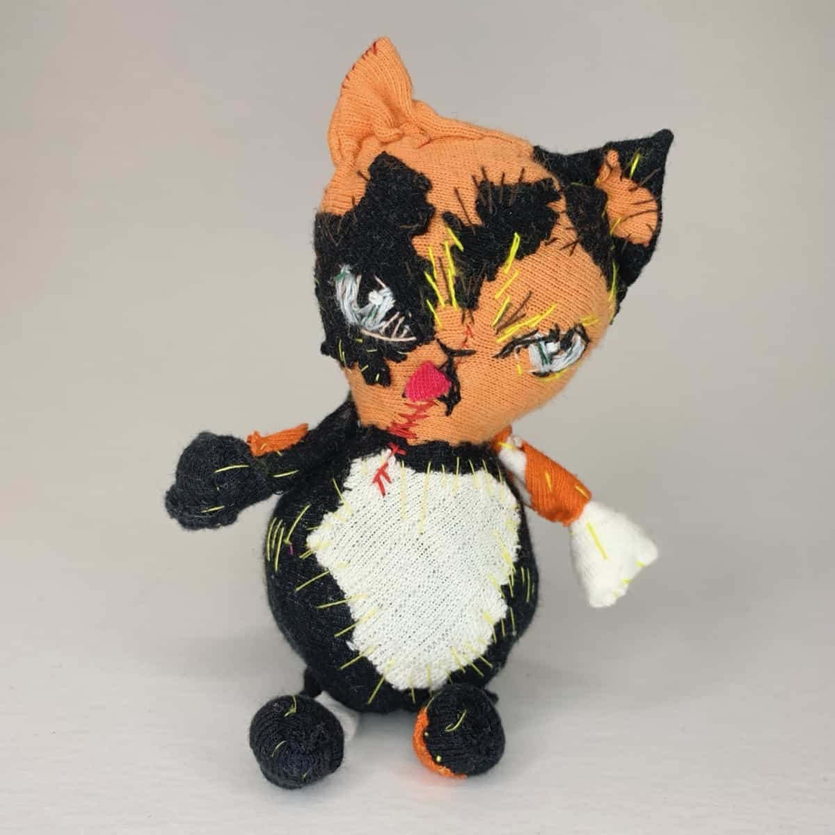 tongue out blue eyes cat made using recycled textile waster